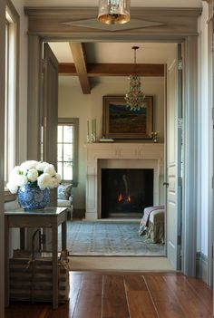 A elegant hallway with wide plank hardwood floors looking into living room with French limestone fireplace. Trim is stained in a Nordic style blue gray. Interior design by Decor de Provence.