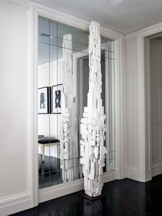 A Louise Nevelson sculpture stands tall in the entryway of a Manhattan apartment | archdigest.com