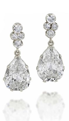 A PAIR OF IMPRESSIVE DIAMOND EAR PENDANTS. Each composed of a brilliant-cut diamond quatrefoil cluster suspending an old-cut pear shape diamond drop weighing approximately 6.30 and 6.96 carats respectively, to plain claw settings, 3.0cm long, post fittings, maker's case Signed Munoa