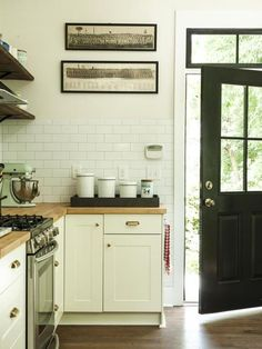 off white subway tile, wooden countertops, simple shaker cabinets and open shelves up top. black door
