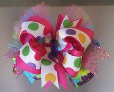 Colorful Boutique Bow- $14.50    This listing is for one Colorful OTT stacked bow. The base bow has bright flowers on it ,blue, purple, pink & green sparkling tulle, sparkling pink spikes, topped with a bright pink bow intertwine with colorful polka dot ribbon, finished with a purple satin middle. The bow is approximately 5 inches across. It is mounted on a French barrette and heat sealed.      https://www.facebook.com/honeybeebows  http://etsy.com/shop/HoneyBeeBowCompany