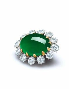 A magnificent oval jadeite cabochon and diamond pendant-brooch, mounted by Carvin French