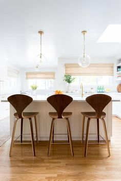 Two Katie Globe Pendants hang over a white kitchen island finished with a white marble countertop holding a prep sink with a Newport brass faucet and seating three Cherner Bar Stools. Kitchen Island Finishes, White Kitchen Island, Kitchen Redo, Kitchen Styling, Kitchen Design, Bright Kitchens, Cool Kitchens, Spanish Kitchen, Mediterranean Home Decor