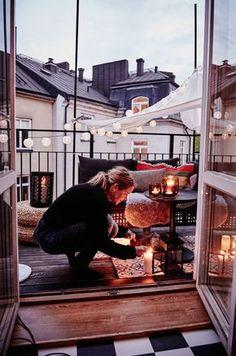 Hyggelig altan med tændte LED lyskæder, en baldakin, lanterner med tændte stearinlys og en sofa fyldt med puder og fåreskind.