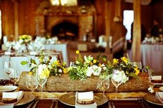 Rustic/country wedding tablescape idea:  flowers in logs for centerpieces.