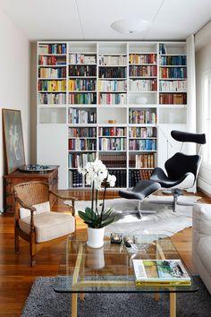 Seinän kokoinen kirjahylly on hankittu Ikeasta. Valaisimet keventävät massiivista hyllykköä. Varierin Tok-lepotuolissa on mukava lukea ja rentoutua. Vanha rottinkituoli ja arkku ovat äidin isoäidiltä. Arkun päällä on sisaren tekemä taulu.