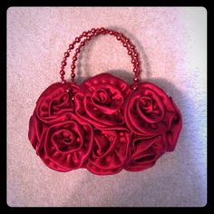 Like New Red Satin Rosette Purse This purse is covered in red satin rosettes and has a red satin interior and beaded straps. it zips closed. It is from Laila Rowe and has only been used once. Bags