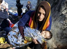 An Afghan migrant carries her baby after arriving by a raft on the Greek island of Lesbos November 19, 2015. REUTERS/Yannis Behrakis