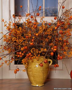 Fall Decorating - bittersweet and other fall branches in golden yellow urn...