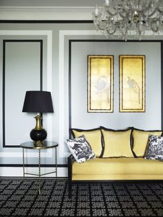 a cheerful canary colored sofa with artwork to match, juxtaposed with moody grey + black hues
