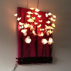 Styrofoam or canvas covered with scrapbook paper.  Add desired branches/flowers (light up flower branch seen here).  Apply fake moss or grass (chocolate grass seen here). Hot glue on to scrap book covered canvas. Hide plug or battery behind canvas.  Best to use battery operated branches (pic shows plug-in)