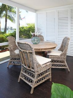 A plantation style veranda space with rattan furniture and dark wood floor by Blackband Home and Design