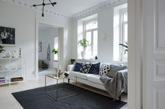 Open sitting room with clean lined, simple furniture and minimal colour palette