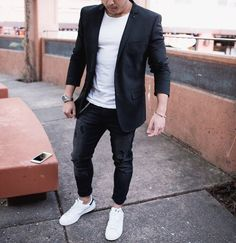 This combination of a black sportcoat and black slim jeans is perfect for a night out or smart-casual occasions. Dress down this getup with white low top sneakers. Shop this look on Lookastic: https://lookastic.com/men/looks/blazer-crew-neck-t-shirt-skinny-jeans/20099 — White Crew-neck T-shirt — Black Blazer — Black Skinny Jeans — Silver Watch — White Low Top Sneakers