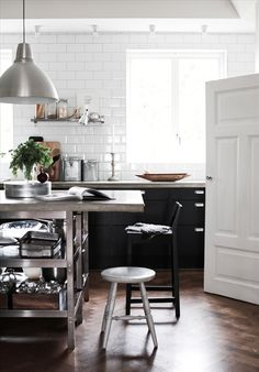 black lower cabinets, white subway tile to ceiling, industrial island, wood floors
