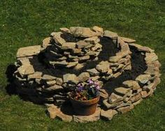 Herb Spiral- plant the dry plants at the top, the water lovers at the bottom. Can be built with brick, stone, cinderblock. Herb Spiral, Spiral Garden, Herb Garden, Flag Pole Landscaping, Garden Landscaping, Permaculture, Culture D'herbes, Dry Plants, Kraut