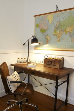 Gorgeous boy's room with vintage roll-down world map hung over an iron based single drawer desk with wood top accented with a lever arm black and nickel desk lamp and a small vintage wooden box.