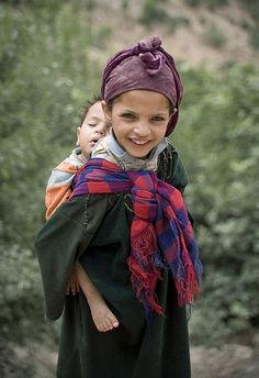 A little girl in Morocco wearing her sibling.