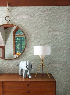 A hanging round mirror and gold tripod table lamp add a grown-up elegance to this kids' bedroom dresser.