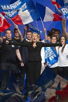 Marine Le Pen, the National Front party leader and their candidate for the 2012 French presidential election, sings the national anthem with supporters on stage at the end of a campaign rally in Paris April 17, 2012.
