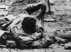 War and Conflict, The Vietnam War, Hue, South Vietnam, pic: February 1968, An American marine passing up some machine gun ammunition as he 'hugs' the ground to avoid sniper fire