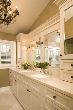 The cabinets.. the sconces, the double mirrors, the chandelier.. This is what bathrooms look like in heaven