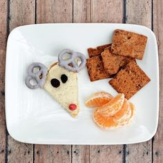 Cute, healthy snack for kids made from Naturebox Cranberry Pepita Crisps, Blueberry Greek Yogurt Covered Pretzels for reindeer antlers, and a few orange slices