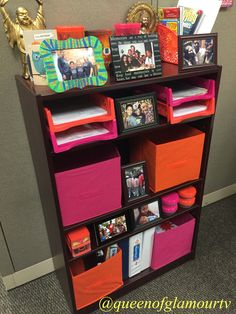 Organize and spruce up any bookcase. I wanted to glam up my office space so I purchase these pink and orange items from dollar tree. Buns and storage can be purchased at thrift stores as well. You can be glam on a budget!! All picture frames are from dollar tree as well . Book case was provided by my job, unsure of details.