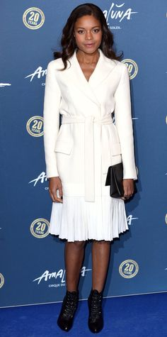 Naomie Harris chose a sleek ivory pleated Dior coat dress that she styled with a black clutch and lace-up booties for an appearance at the Cirque Du Soleil: Amaluna performance.