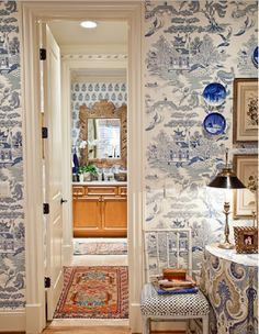 Eric Ross Interiors ~ Anthropologie Wallpaper ~ Such a dramatic room with the blue and white wallpaper that is shown with a coordinating wallpaper continued on to what appears to be the bathroom.  The fabric used on the table coordinates beautifully.