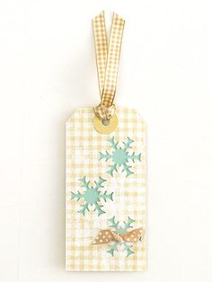 Decorate Plain Gift Tags for Christmas into a  Snowflake Tag - Add color to the front of a  white gift tag with a stamp or a design painted freehand. Then punch out snowflake shapes and back the tag with a piece of colored paper.