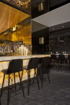 Restaurant in Paris, detail of the onyx stone countertop and brass box bar, interior design by Rodolphe Parente and Benjamin Liatoud