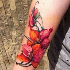 Colorful Orchid Tattoo. This orchid design is really beautiful and colorful. The colors used in this tattoo makes it look cheerful and enchanting.