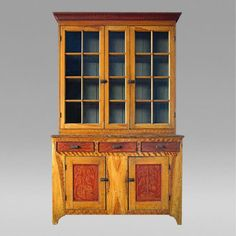 Paint Decorated Cupboard, Circa 1810-1820 from Lehigh,PA Origin United States, Pennsylvania  Creation Date Circa 1810-1820  Dimensions  W. 58 in;  H. 90 in;  D. 20 in;   W. 147.32 cm;  H. 228.6 cm;  D. 50.8 cm;         Description In two parts. Upper section has two eight-pane doors with four intermediate panes, beautiful balance, step down mullions and wonderful faux-grain paint design overall. Dovetail construction, original blue/green interior paint with spoon slots built into shelves