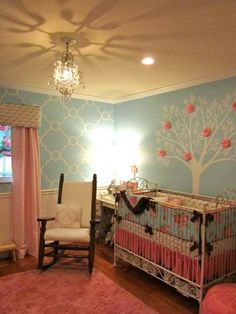 Charming light blue and pink baby girl nursery decor featuring a tree wall mural with pink flowers.  #cutenurserydecor #girlnurseryideas
