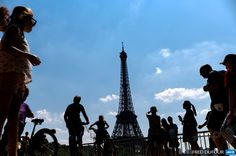 FRANCE, Paris: Tourists walk in front of the Eiffel Tower on July 9, 2013 in Paris. AFP PHOTO / FRED DUFOUR