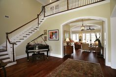 FOYER – great example of an impressive way to welcome guests. Bring in the baby grand. Some foyers are so large that they need bigger items that will stand up to the scale. A piano is the right size for this staircase corner, and the ivories tickled here can probably be heard all over the house.
