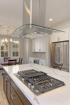 Della Terra Nouveau Quartz Countertop with Large Gas Cooktop and Range Hood Photo by Preview First