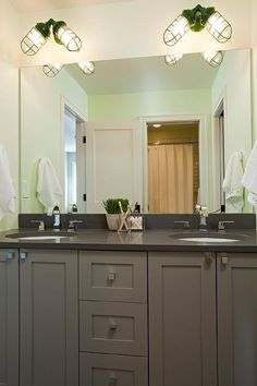 Grey kid's bathroom is filled with a gray dual vanity adorned with square knobs topped with charcoal gray quartz fitted with his and hers sinks under a full length frameless mirror illuminated by green cage sconces.