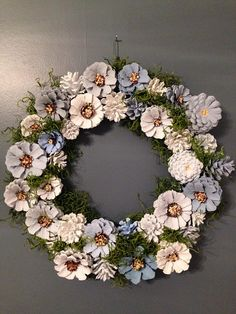 This pine cone wreath in shades of blue and gray is my most popular wreath. Pine cones are hand painted and wired allowing it to be used outside but preferably under a covered porch where it wont get wet. Wreath is 13.5 x 13.5 in diameter and embellished with spanish moss. Wreath is sprayed with a clear acrylic gloss coating.