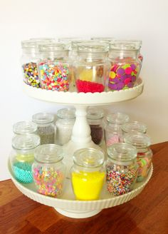 Sprinkles stored/displayed in spice jars on cake stands.