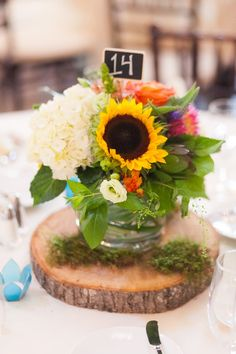 Mason jar centerpieces atop wooden tree slices draped with moss, chalkboard numbers, and votive candles - love! {Wilton Brothers Photography}