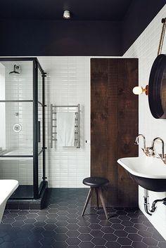 industrial feel bathroom with steel framed shower enclosure and black hexagon floor tile. / sfgirlbybay