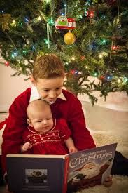 Big brother reading a Christmas tale to his baby sister
