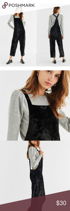 UO Crushed Black Velvet Street-Style Overall No-frills overall in the perfect relaxed fit. Luxe-to-the-touch fabrication that drapes the body with super-low sides + slim cross-strap racerback. Finished with a cropped straight-leg. Perfect for layering. Urban Outfitters Pants