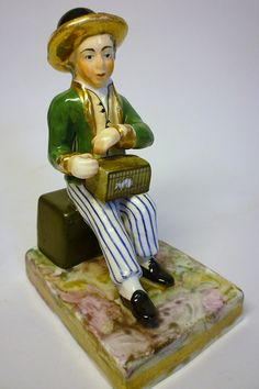 "Staffordshire porcelain figure of a boy with a white rat in a cage. This is a small figure, just over 4"" high and very unusual. Is he a street entertainer or just a lad with a pet rat?I'd love to find a source for this."