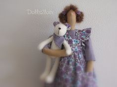 Tilda doll Nicky wearing a purple gingham dress and a pink liberty fabric pinafore accompanied by her little teddy bear made by Dolls2love on Etsy, €47.50.