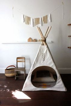 I love the round opening in this teepee (tipi). Simple and a perfect nook for the playroom.