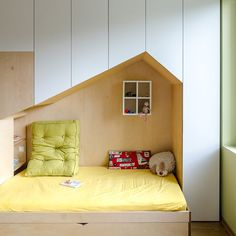 This fun and modern kid's bedroom has a custom wall unit that features plenty of storage and two beds in mini houses.