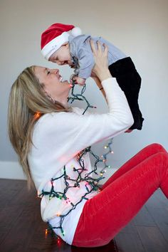 Wrapping the lights around my pregnant belly & holding Ivan in the air! Hunter green shirt & jeans  Jeans & red shirt